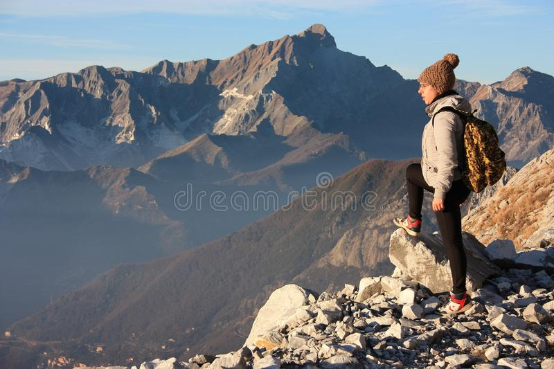 A young woman makes trekking on a mountain royalty free stock images