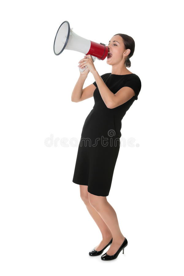 Young woman making a announcement. Full length of young woman making announcement over megaphone on white background royalty free stock images