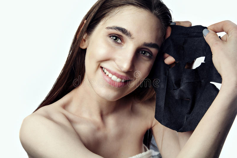 Young woman is making a beauty face black mask to cary on skin royalty free stock photo