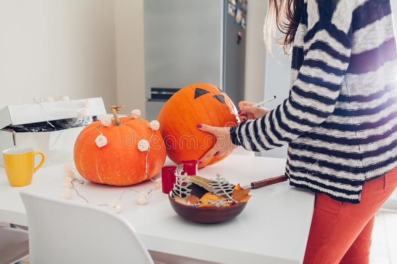 Young woman making jack-o-lantern for halloween on kitchen. Drawing eyes, nose and mouth with pen on pumpkin royalty free stock photography