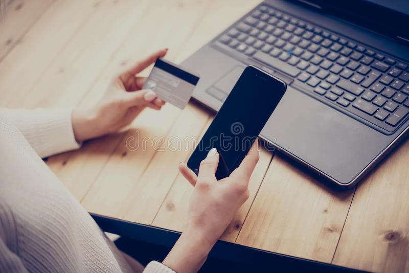 Young woman making online shopping by laptop and smartphone.Girl touching home button on mobile phone, writing security. Number of credit card.Horizontal royalty free stock photo