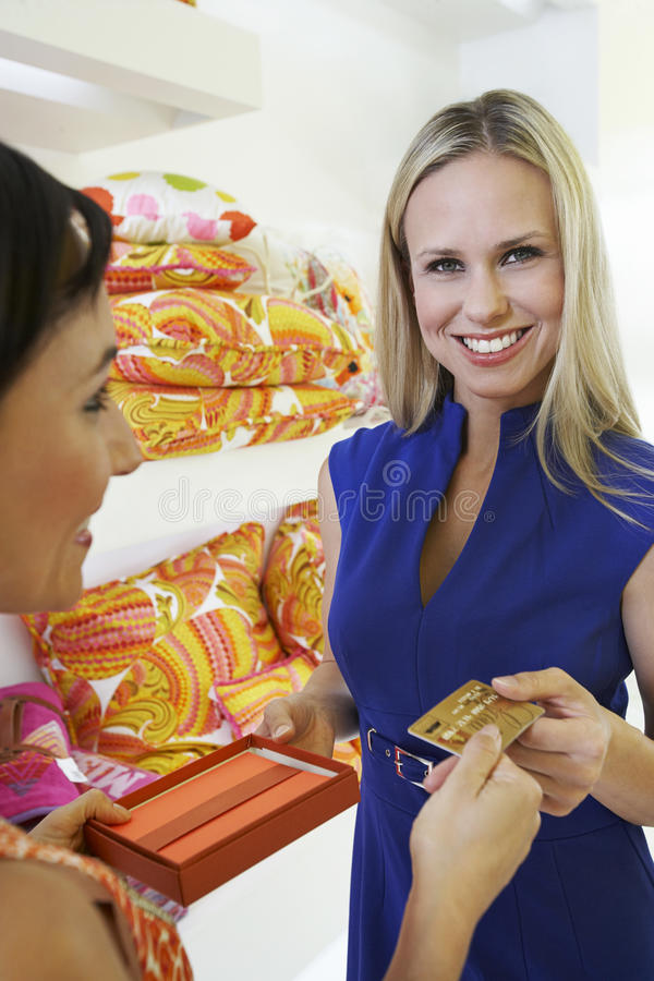 Young Woman Making A Purchase. Beautiful blonde women paying for purchase with credit card in store royalty free stock images