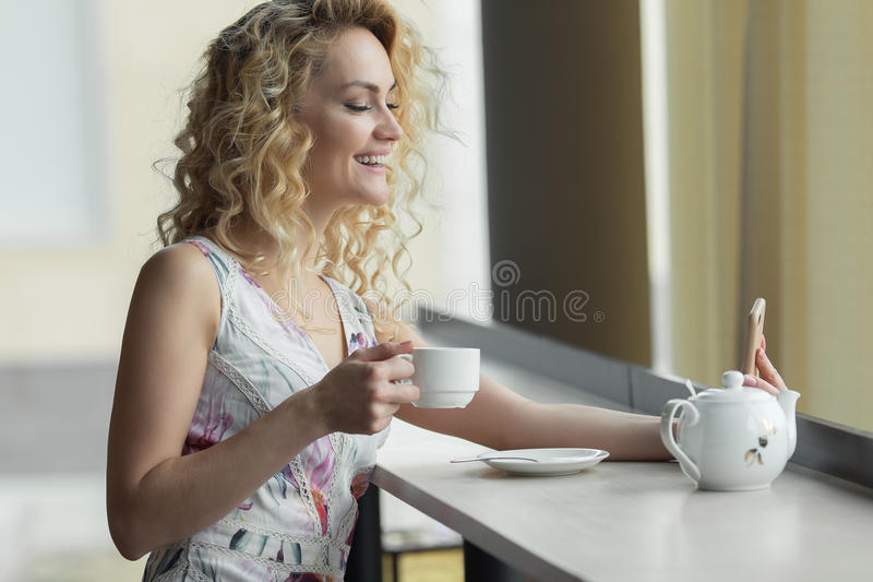 Young woman making self portrait on her smart phone digital camera while sitting in cafe during lunch break. royalty free stock photo