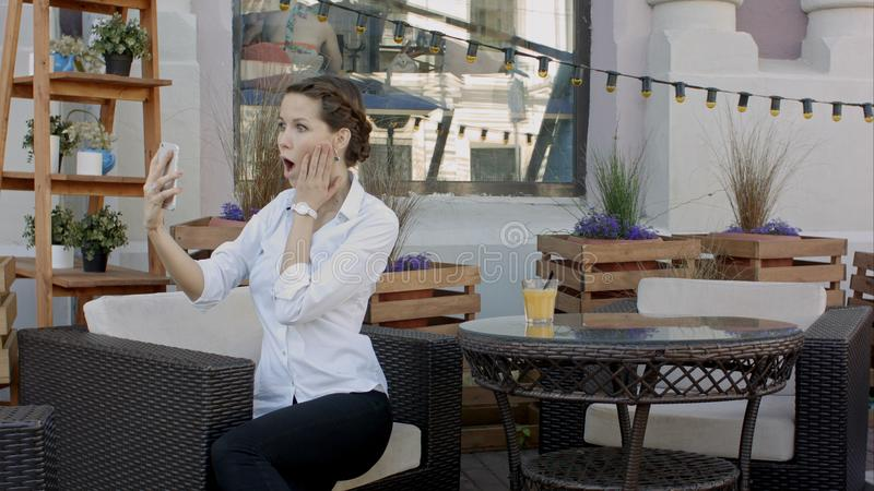 Young woman making self portrait using smartphone. girl making selfie. woman in cafe. woman alone. self portrait in cafe royalty free stock photos