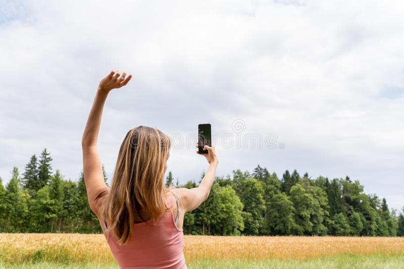 Young woman making selfie with her mobile phone outside royalty free stock photos