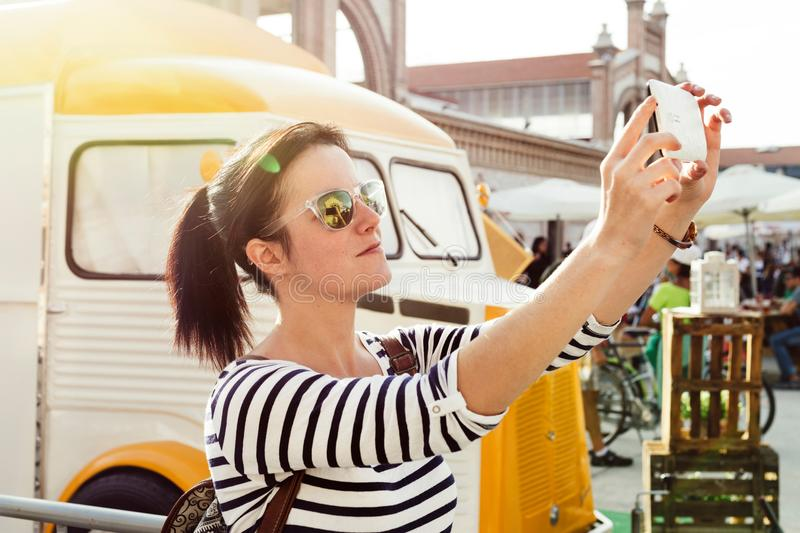 Young woman making a selfie, next to the food truck stock photography