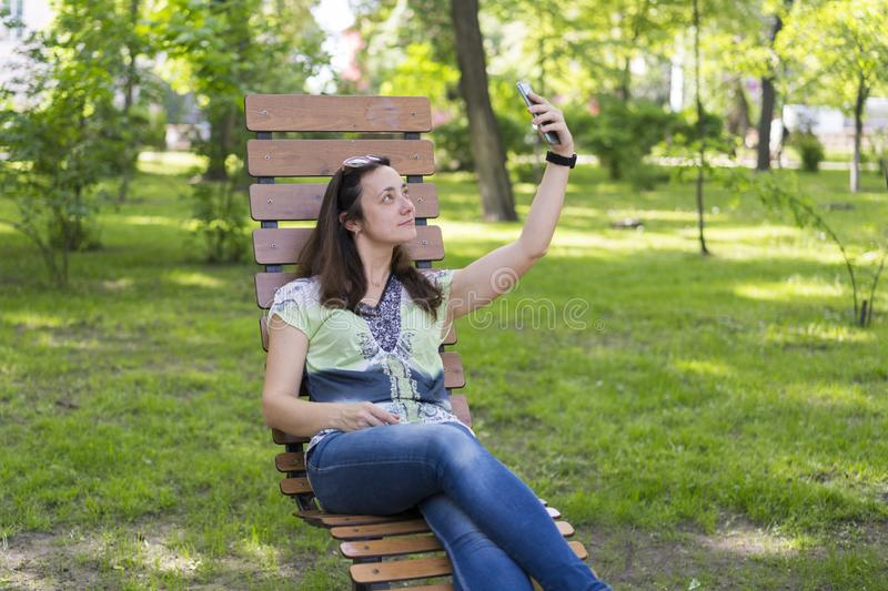 Young woman making selfie in the park. Sexy young woman with long blond hair doing selfie on summer day in park. Cheerful girl royalty free stock images