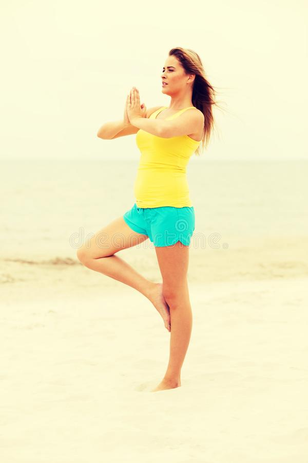 Young woman making yoga exercises on the beach stock photos