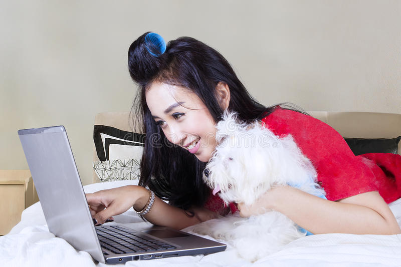 Young woman with Maltese dog and laptop royalty free stock image