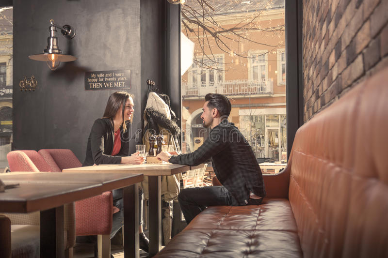 Young woman man couple friends, sitting table cafe shop, talking stock image