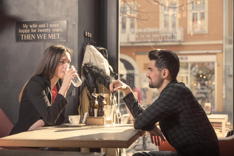 Young woman man couple friends, sitting table cafe shop royalty free stock images