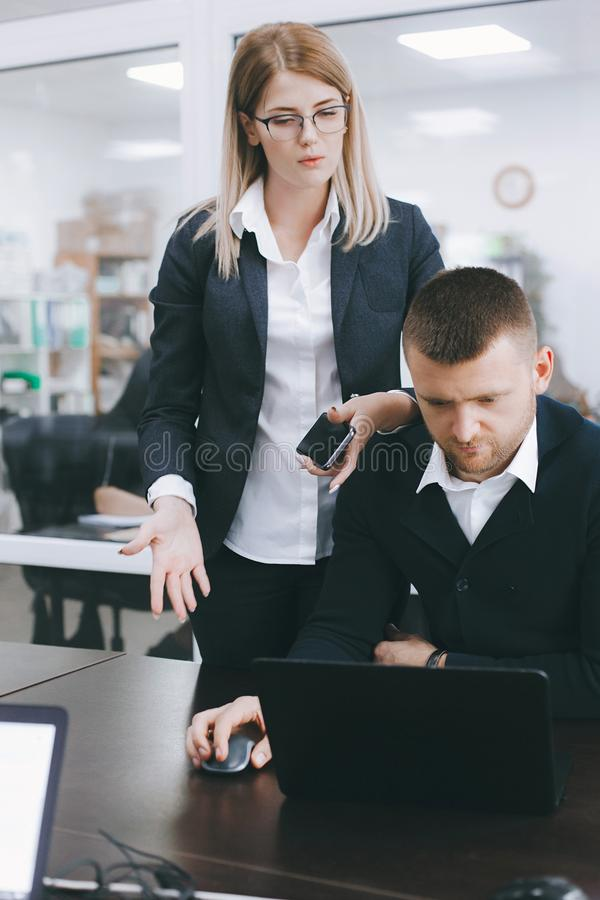 Young woman and man discuss work at table in office royalty free stock images