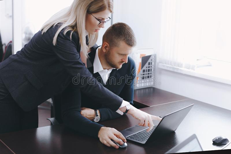 Young woman and man discuss work at table in office stock images