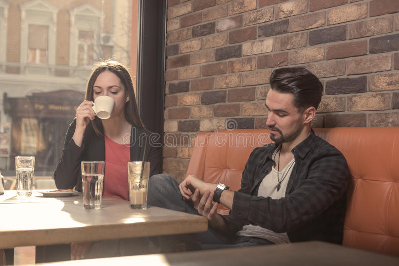 Young woman man, drinking, looking at watch caffe stock image