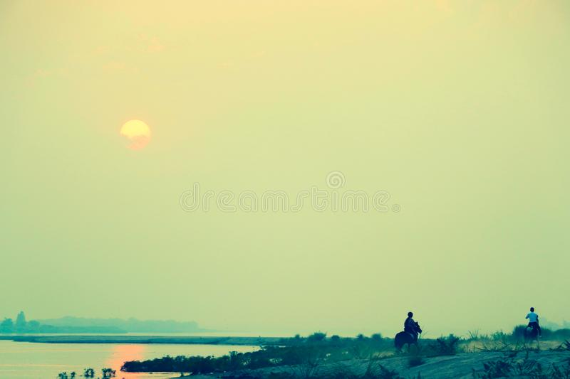 A young woman and a man enjoy riding on the horse on the beach along the riverside towards to the sunset direction royalty free stock image