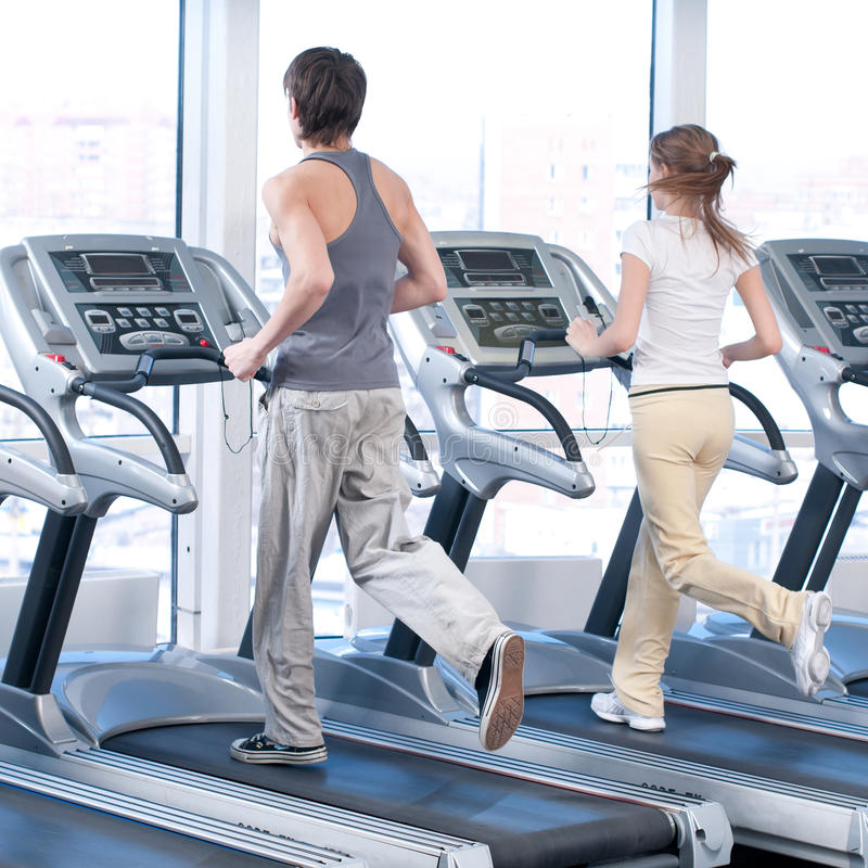 Young woman and man at the gym exercising. Running. Young woman and man at the gym exercising. Run on on a machine royalty free stock photo