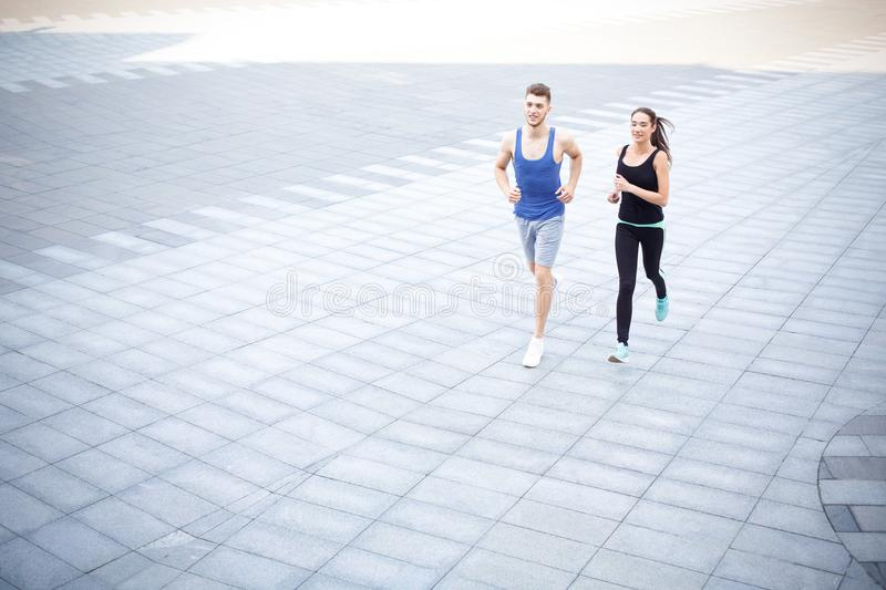 Young woman and man running in city copy space stock photo