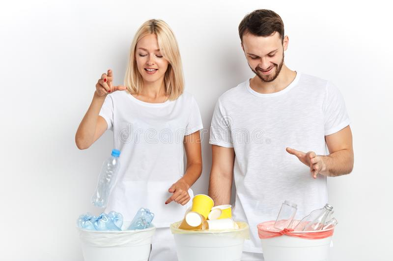 Young woman and man separate waste and recycling it at workplace. Young cheerful happy women and men separate waste and recycling it at workplace, good habit stock images