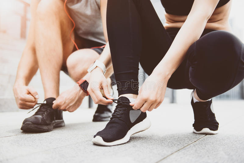 Young woman and man tying shoelaces before training royalty free stock photos
