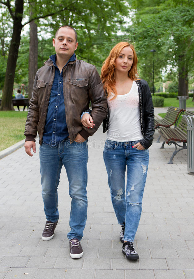 Young woman and man walking in city park. Young women and men walking in city park holding hands royalty free stock images