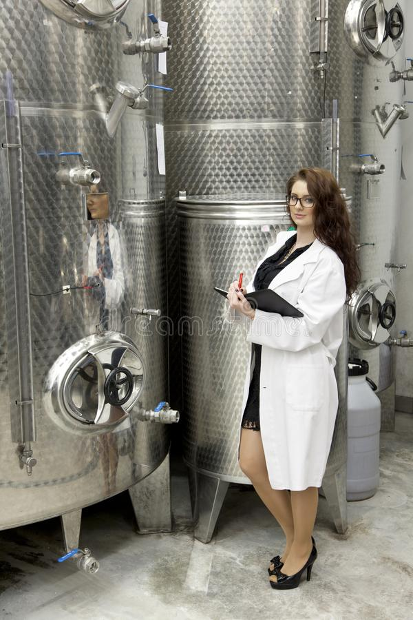 Young woman manageress is standing in front of steel cylinder of large stainless steel tank in chemical manufacturing. stock image