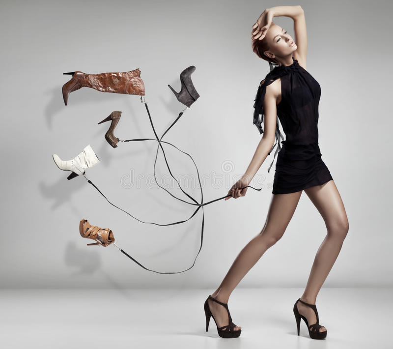 Young woman with many shoes.  stock photo