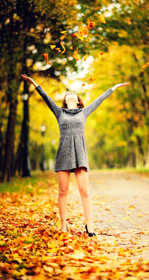 Young woman in maple leaves in autumn park stock photo