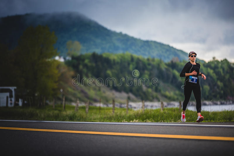 Young Woman Marathoner at about 7km of distance Alone on the sid. CARLETON, CANADA - June 4, 2017. During the 5th Marathon of Carleton in Quebec, Canada. Young royalty free stock photo