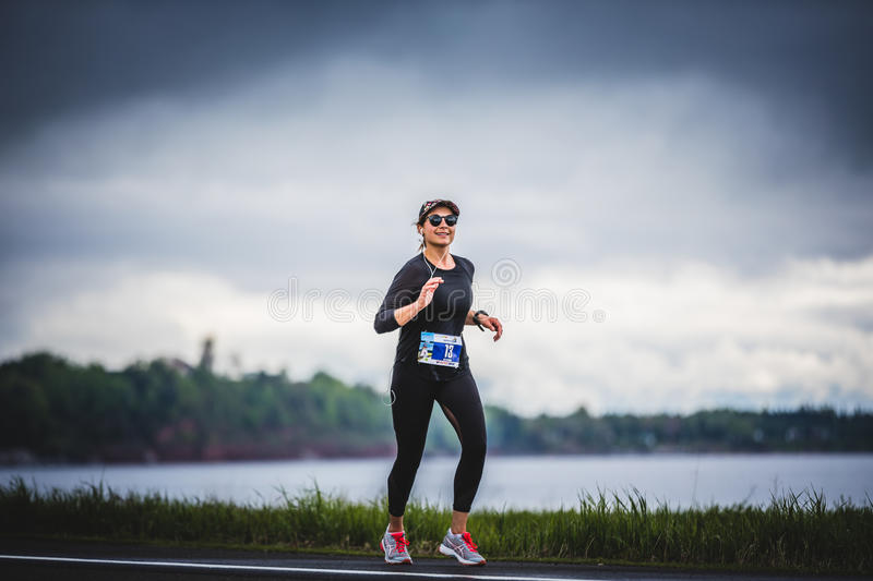 Young Woman Marathoner at about 7km of distance Alone on the sid. CARLETON, CANADA - June 4, 2017. During the 5th Marathon of Carleton in Quebec, Canada. Young stock photos