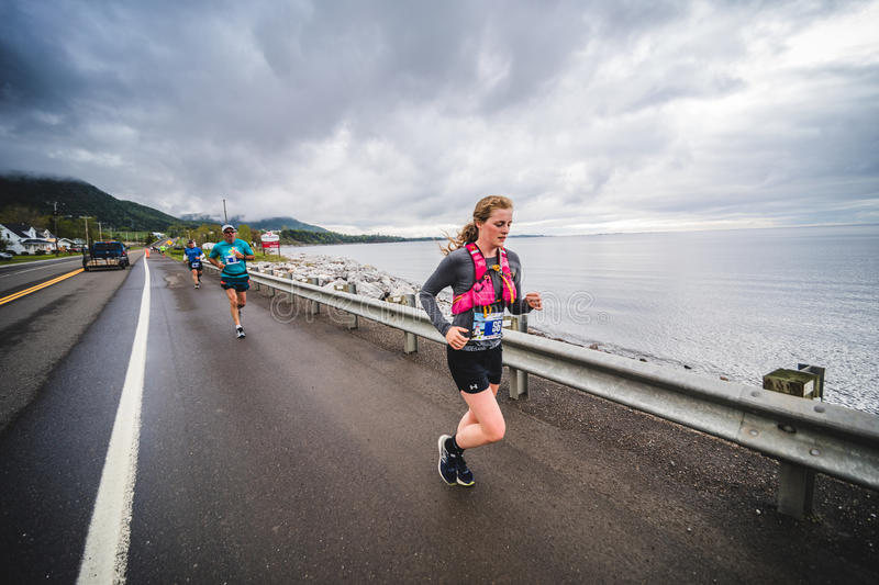 Young Woman Marathoner Leading on the side of the Road and Ocea. CARLETON, CANADA - June 4, 2017. During the 5th Marathon of Carleton in Quebec, Canada. Young stock photo