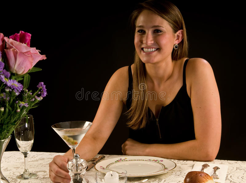 Young woman with martini. Beautiful young woman enjoying her martini at a restaurant, wedding reception, or in a dining room stock photography
