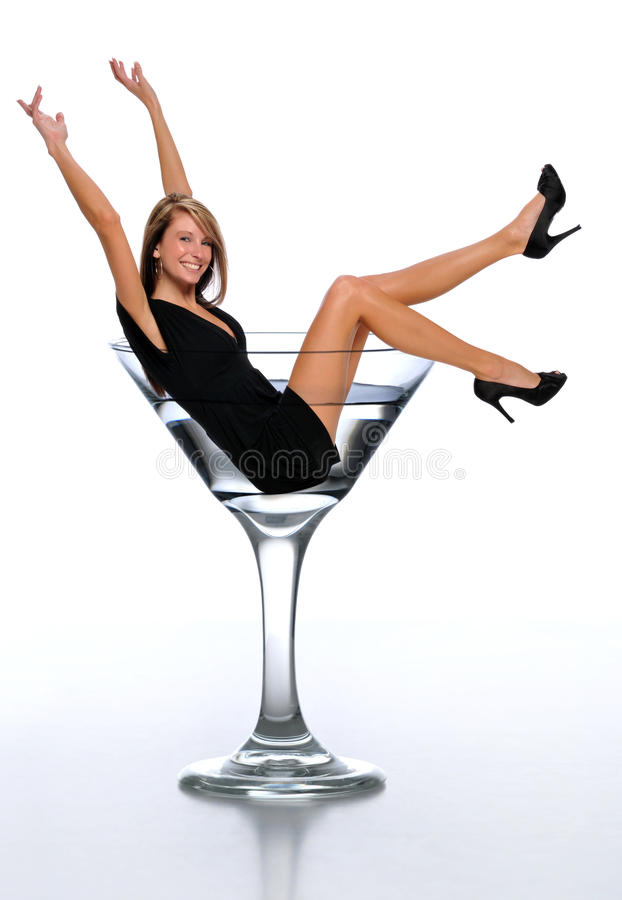 Young woman in a martini glass. Celebrating ans isolated on a neutral background stock photos