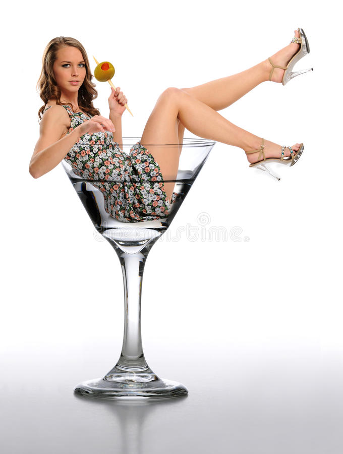 Young Woman in a Martini Glass. Holding an olive against a neutral background royalty free stock photography