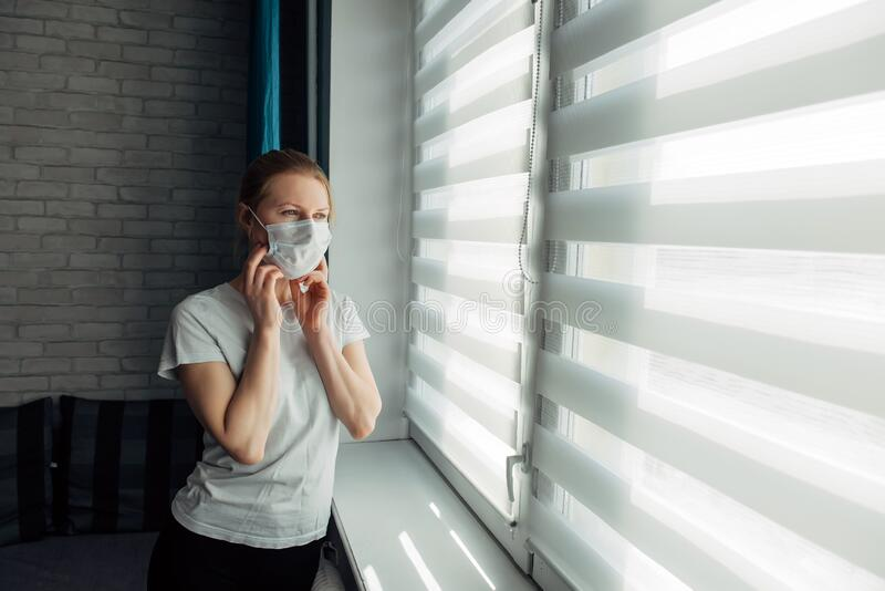 Young woman in mask looking through the blinds. Quarantined coronavirus person. Stay home. Stop the pandemic. Self-isolation,. Putting up mask stock photos