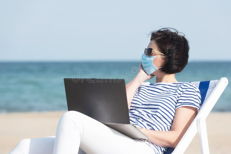 Young woman in a mask sitting with laptop on empty coast, protective equipment during coronavirus covid19. Social royalty free stock photo