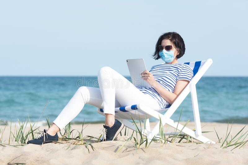 Young woman in a mask sitting with laptop on empty coast, protective equipment during coronavirus covid19. Social royalty free stock photography