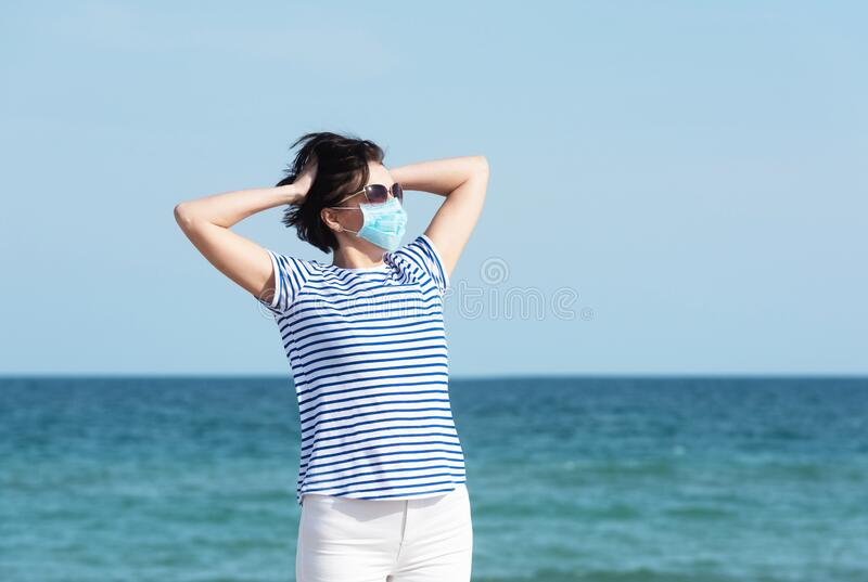 Young woman in a mask standing on empty coast, protective equipment during coronavirus covid19. Social distance concept. stock images