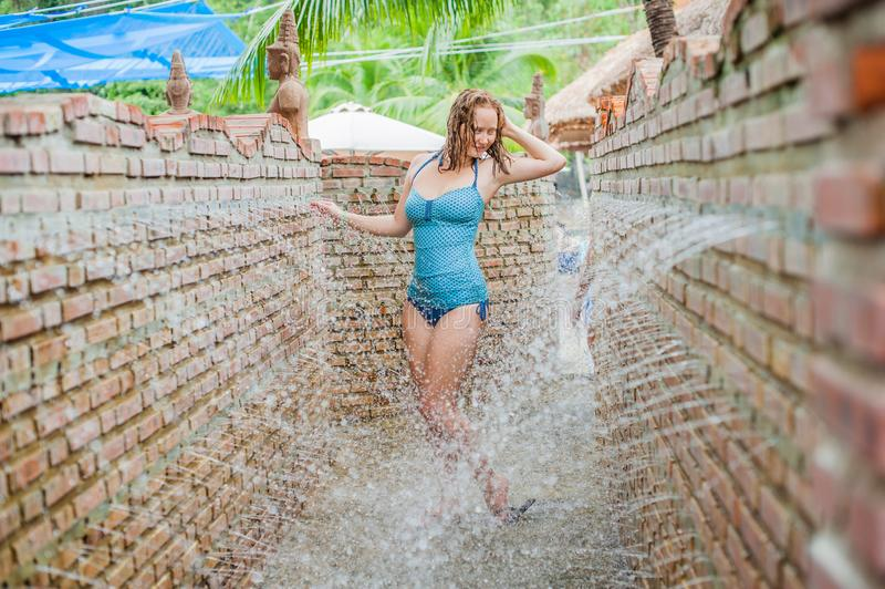 A young woman in the massage shower from the wall royalty free stock image