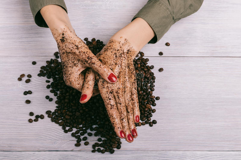 Young woman massaging a hand with coffee scrub. Top view stock images