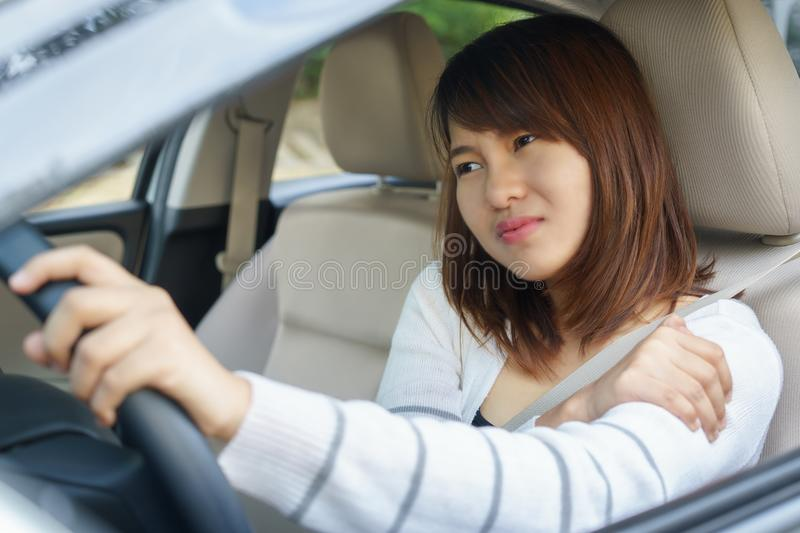 Young woman massaging her arm or shoulder while driving a car af stock photography
