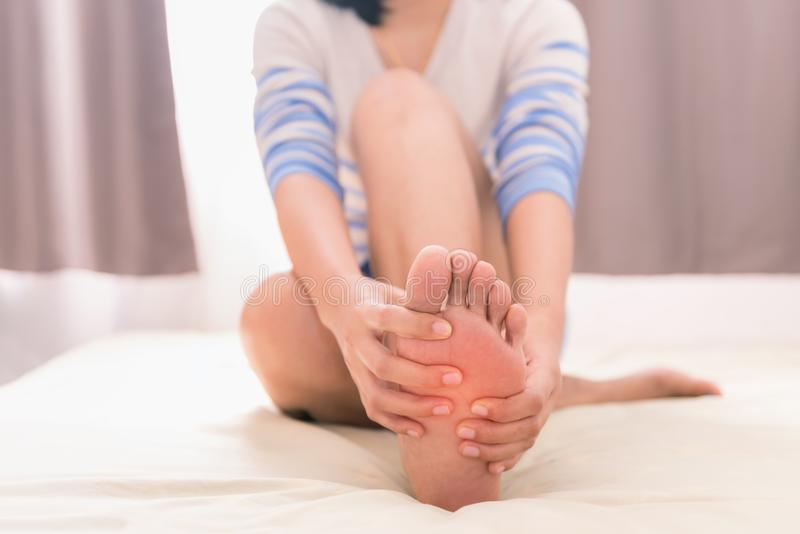 Young woman massaging her foot on the bed, Healthcare concept royalty free stock photos