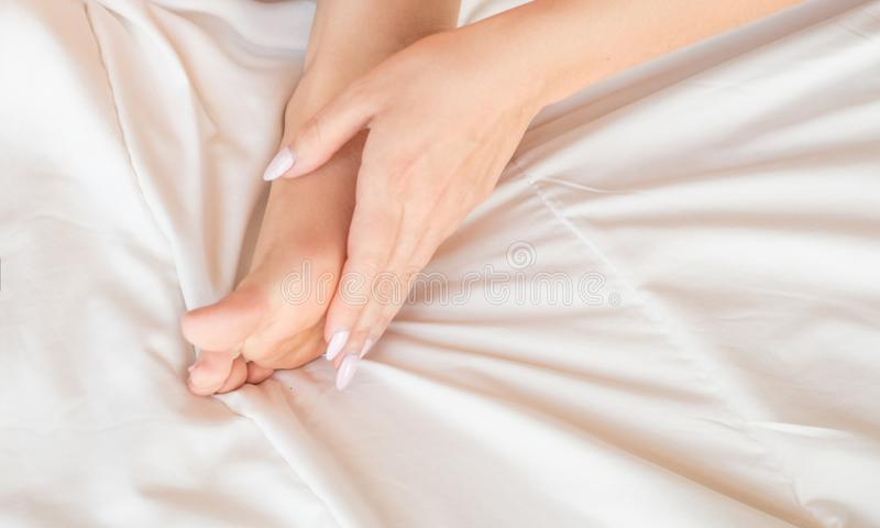 Young woman massaging her foot on the bed., Healthcare concept. royalty free stock photo