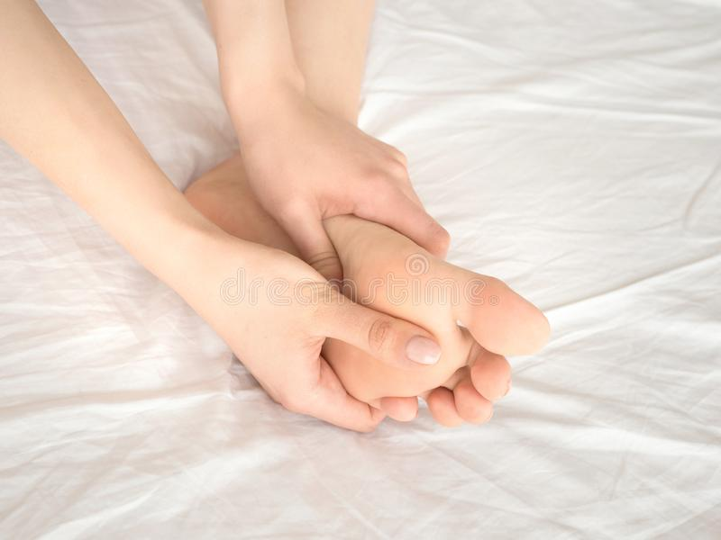 Young woman massaging her foot on the bed. Healthcare concept. royalty free stock photography
