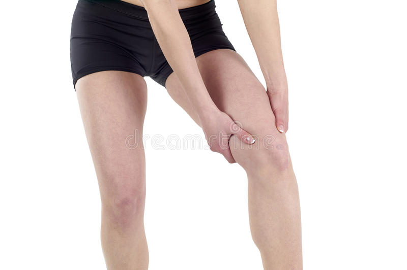 Young woman massaging her painful knee royalty free stock photography
