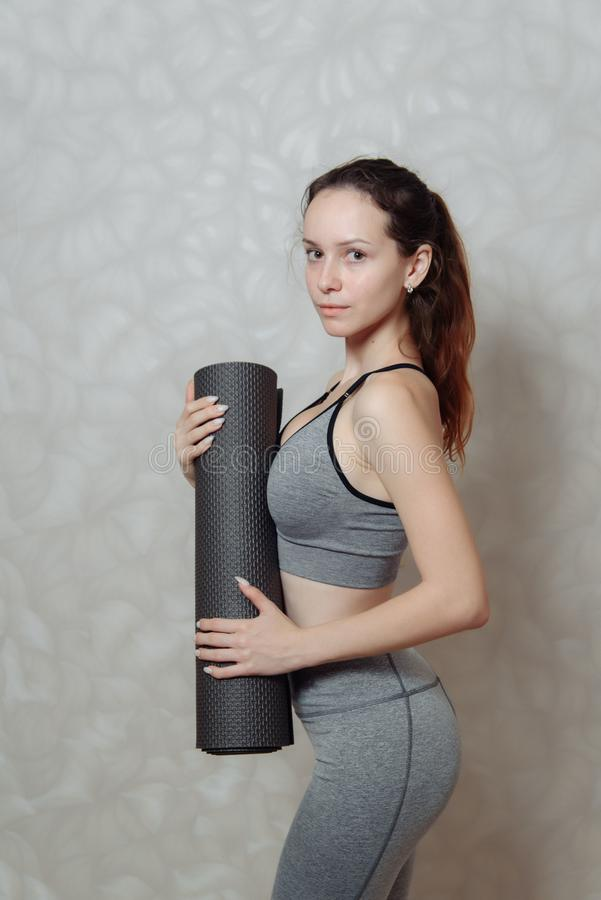 Young woman with a Mat for gymnastics in her hands. a fragment of a woman`s body in sportswear for Pilates and yoga. Young woman with a Mat for gymnastics in her stock photography