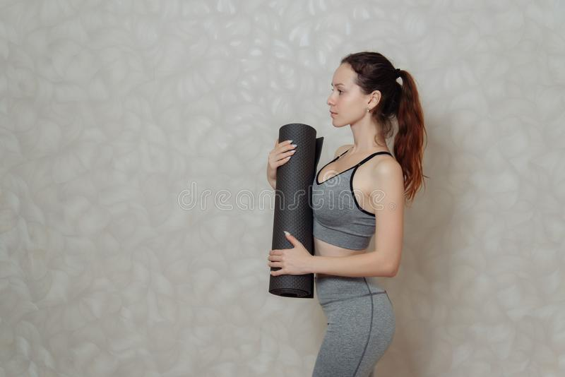 Young woman with a Mat for gymnastics in her hands. a fragment of a woman`s body in sportswear for Pilates and yoga. Young woman with a Mat for gymnastics in her stock image