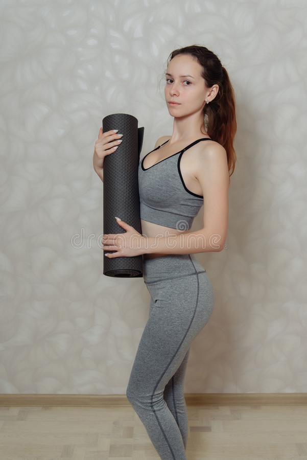 Young woman with a Mat for gymnastics in her hands. a fragment of a woman`s body in sportswear for Pilates and yoga. Young woman with a Mat for gymnastics in her royalty free stock photos