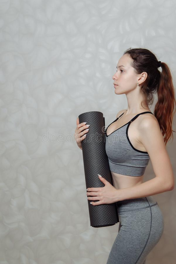 Young woman with a Mat for gymnastics in her hands. a fragment of a woman`s body in sportswear for Pilates and yoga. Young woman with a Mat for gymnastics in her stock images