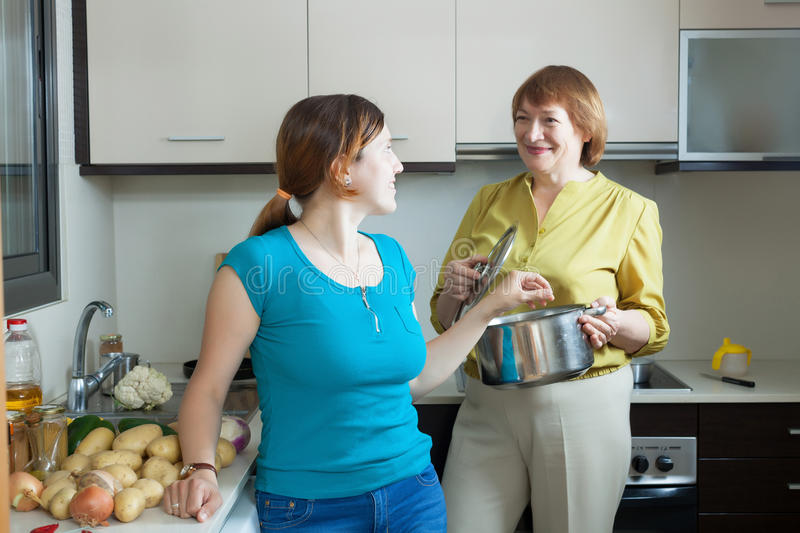 Young woman and mature mother cooking lunch royalty free stock photos