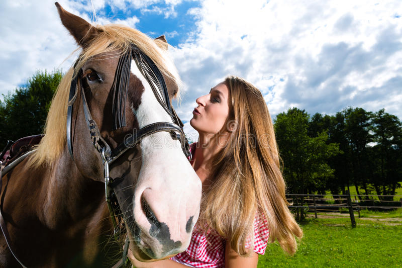Young woman on the meadow with horse and kissing royalty free stock photo